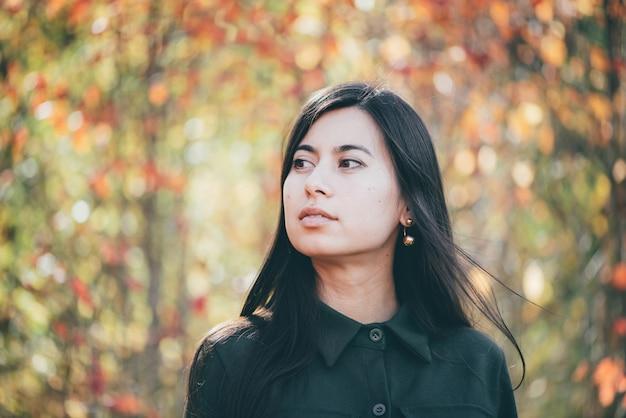 Retrato de menina em fundo de bokeh de outono.