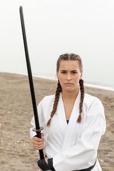 Retrato de menina em traje de karatê com espada