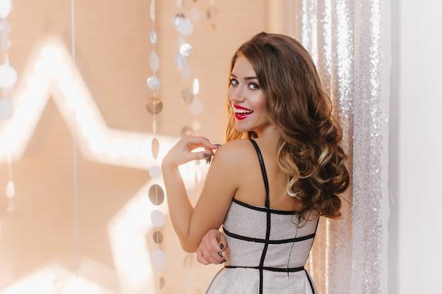 Retrato de menina em um vestido elegante na festa. senhora coquete com lindos cabelos ondulados maliciosamente com sorriso.