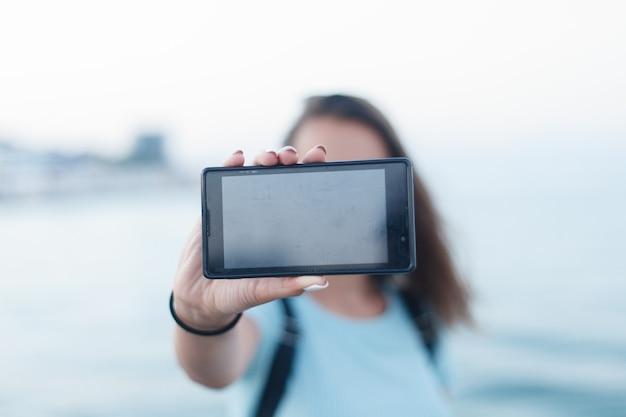 Retrato de menina em uma praia de férias tirando uma selfie