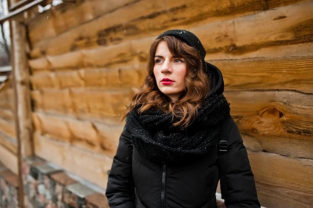 Retrato de menina encaracolado morena de jaqueta preta, chapéu e lenço em dia de inverno.
