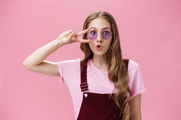 Retrato de menina energética elegante com cicatriz na mão, mostrando o símbolo da paz sobre o olho, usando óculos escuros legais e macacão de veludo cotelê, dobrando os lábios, fazendo um rosto bonito tirando foto contra o fundo rosa.