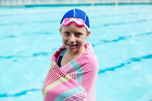 Retrato de menina enrolada em uma toalha em pé à beira da piscina
