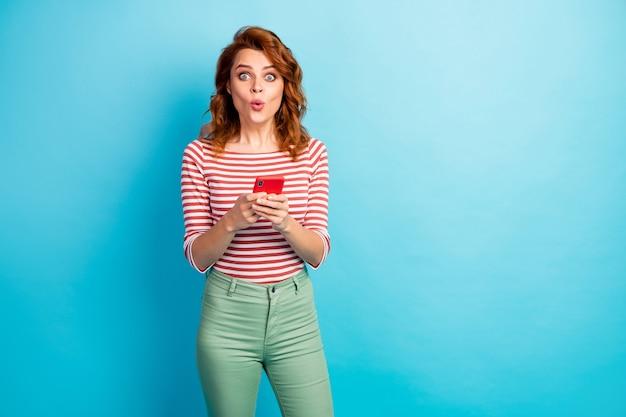 Retrato de menina espantada, usando o telefone celular, lendo informações da rede social, impressionado, grito, nossa, use uma roupa bonita isolada sobre a cor azul