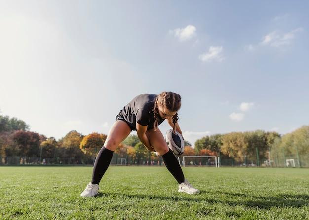 Retrato de menina esportiva segurando uma bola de rugby