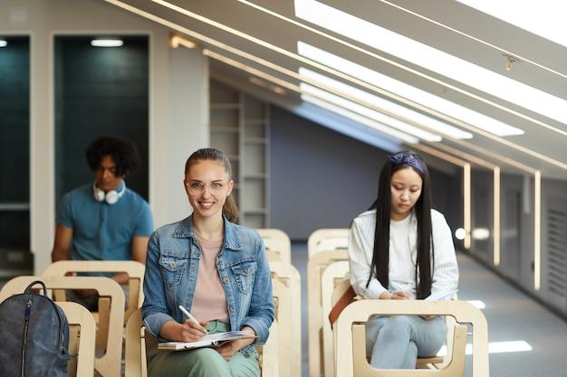 Retrato de menina estudante positiva em jaqueta jeans, sentada na cadeira durante a palestra e fazendo anotações no diário