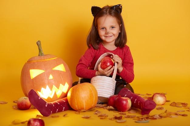 Retrato de menina fantasiada de gato, criança sentada no chão com uma cesta de doces ou travessuras, cercada com maçãs e jack o lantern