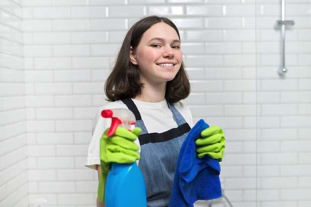 Retrato de menina fazendo limpeza no banheiro. adolescente em luvas de avental com detergente e esponja de pano sorri olhando para a câmera. limpeza, limpeza em casa, serviço, conceito de jovens