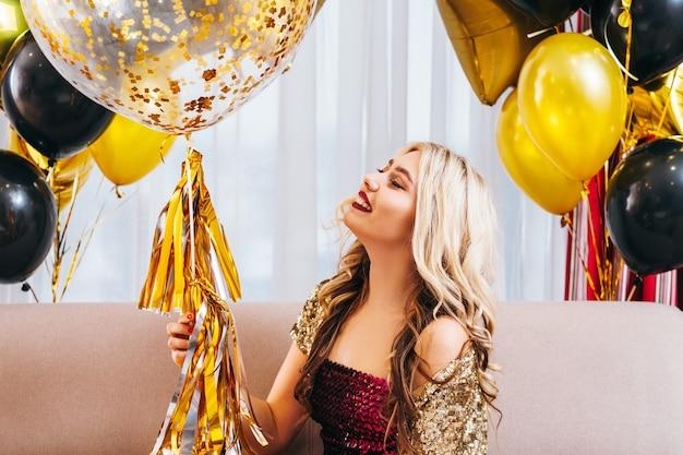 Retrato de menina feliz aniversário, sentado na sala decorada com balões. senhora loira sorrindo, apreciando a celebração.