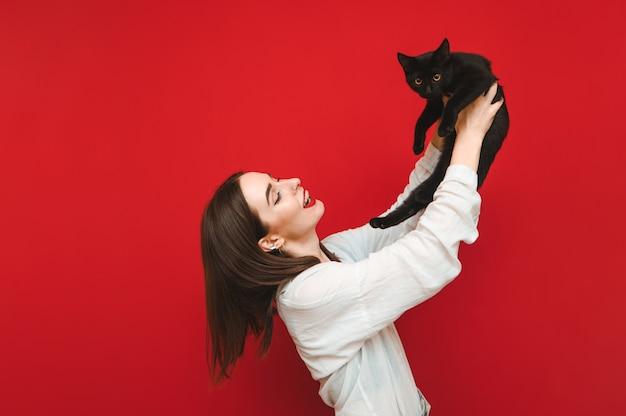 Retrato de menina feliz brincando com gato