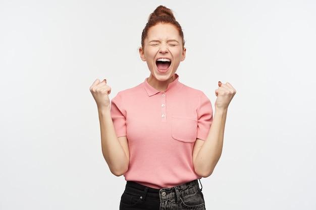 Retrato de menina feliz, celebrando com coque ruivo.