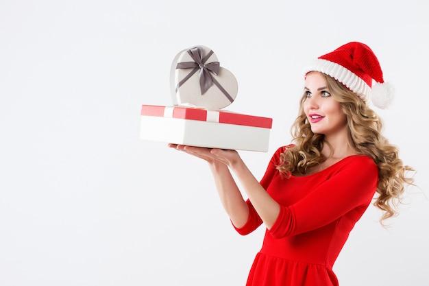 Retrato de menina feliz com chapéu de papai noel e caixas de presente