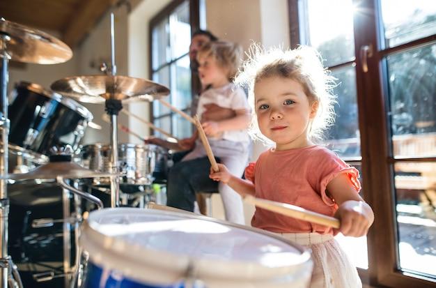 Retrato de menina feliz dentro de casa em casa, tocando bateria.