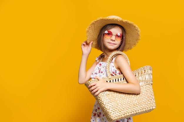 Retrato de menina feliz e alegre em bolsa de palha de óculos de sol de chapéu de verão sobre fundo amarelo