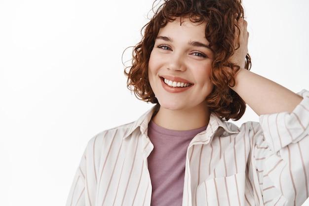 Retrato de menina feliz e cândida com pose relaxada, sorriso branco alegre e penteado curto encaracolado elegante, tocando o cabelo e parecendo alegre para a câmera em branco