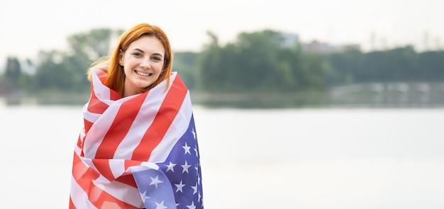 Retrato de menina feliz e sorridente com a bandeira nacional dos eua nos ombros. mulher jovem positiva comemorando o dia da independência dos estados unidos.