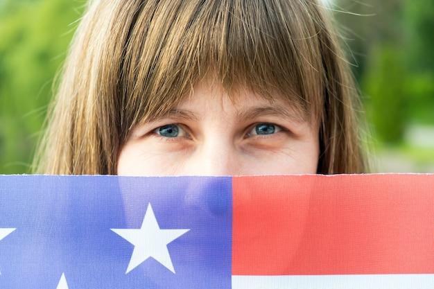 Retrato de menina feliz e sorridente, escondendo o rosto atrás da bandeira nacional dos eua. dia internacional do conceito de democracia.