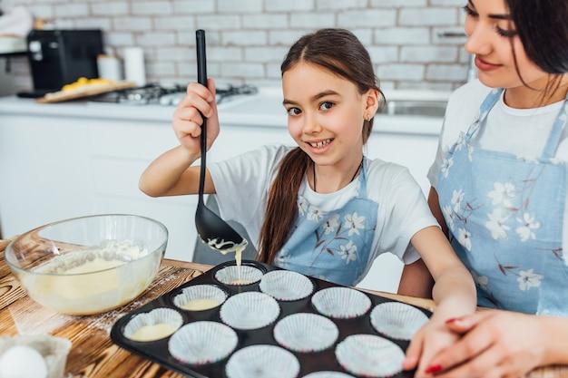 Retrato de menina feliz fazendo cupcakes com a mãe