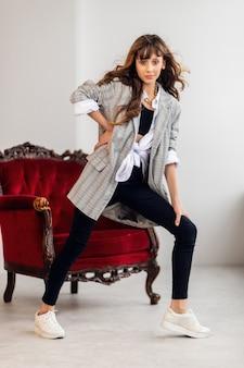 Retrato de menina feliz. menina com uma jaqueta cinza, em um interior torto com uma poltrona cor de vinho. tênis branco. moda infantil, crianças felizes. modelo de menina