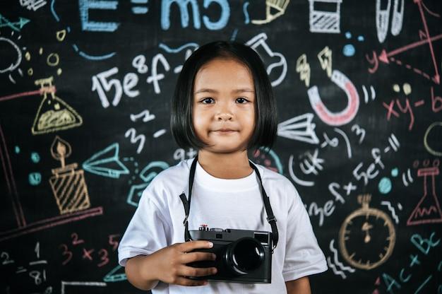 Retrato de menina feliz segurando uma câmera digital, menina fotógrafa gosta de usar a câmera para tirar uma foto