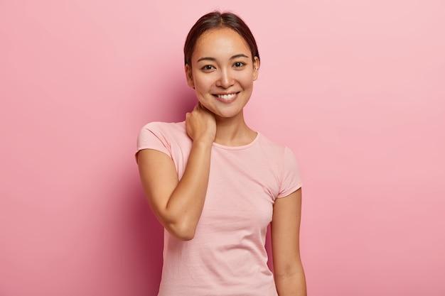Retrato de menina feminina com sorriso agradável, olhar gentil, toca o pescoço, tem expressão facial encantada, conversa agradável com amiga próxima, vestida com roupa casual, isolada na parede rosa