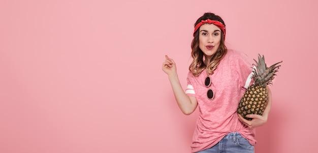 Retrato de menina hippie de óculos e abacaxi na parede rosa