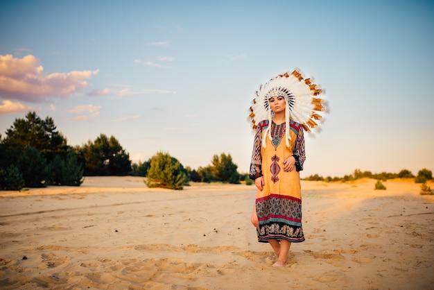 Retrato de menina índia americana em traje tradicional e cocar feito de penas de pássaros selvagens