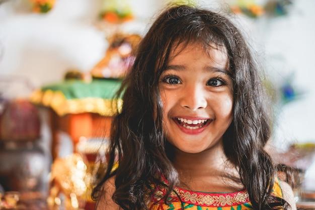 Retrato de menina indiana feminina com vestido sari - criança do sul da ásia se divertindo, sorrindo - infância, diferentes culturas e conceito de estilo de vida