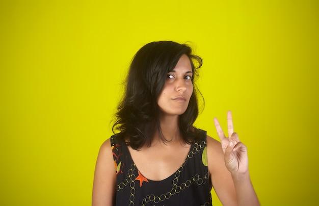 Retrato de menina indiana mostrando os dedos fazendo o sinal da vitória ou o número dois
