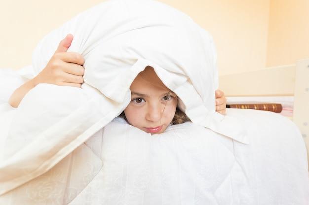 Retrato de menina irritada cobrindo o travesseiro e não quer se levantar