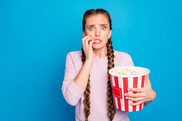 Retrato de menina jovem assustada assistir série de terror segurar caixa com pipoca sentir medo morder unhas usar roupas bonitas isoladas sobre fundo de cor brilhante