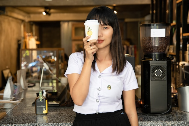 Retrato de menina jovem bonita escola asiática na cafeteria