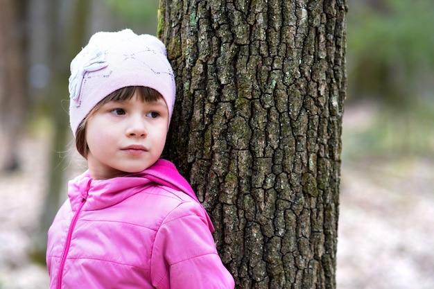 Retrato de menina jovem criança bonita vestindo jaqueta rosa e boné, inclinando-se para uma árvore na floresta, aproveitando o dia ensolarado quente no início da primavera ao ar livre.