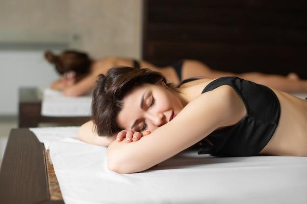 Retrato de menina jovem modelo linda em espreguiçadeiras de madeira relaxantes na sauna