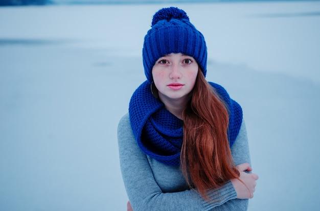 Retrato de menina jovem ruiva com sardas vestindo azul chapéu de lã e cachecol em dia de inverno.