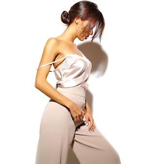 Retrato de menina linda mulher morena sensual em elegantes roupas clássicas brancas e calças largas no fundo branco