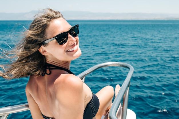 Retrato de menina linda sorridente feliz em óculos de sol no iate