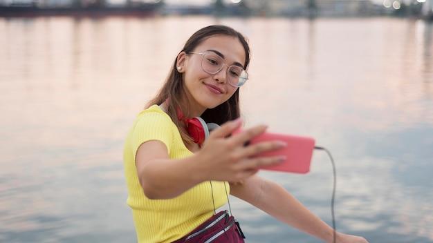 Retrato de menina linda tomando uma selfie