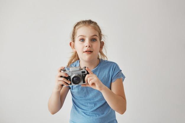 Retrato de menina loira bonita de camiseta azul, segurando a câmera nas mãos com expressão concentrada, indo tirar uma foto de gato bonito na rua.