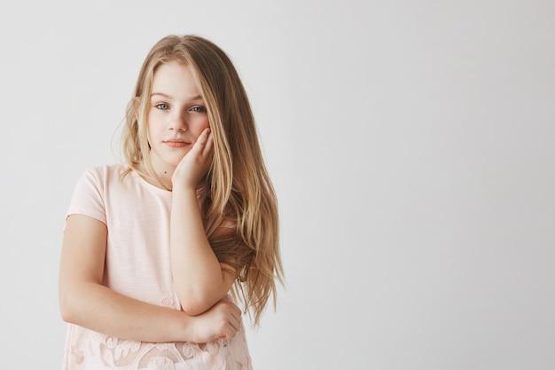 Retrato de menina loira bonitinha em camiseta rosa, segurando a cabeça com a mão, estar cansado e entediado durante as aulas.