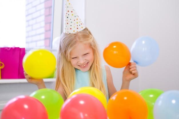 Retrato de menina loira caucasiana, sorrindo para a festa de aniversário de câmera. fundo colorido festivo com balões. foto vertical