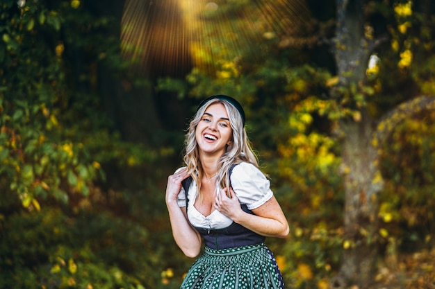 Retrato de menina loira e bonita feliz em vestidos casuais, festival tradicional de cerveja, ao ar livre com árvores coloridas blured atrás