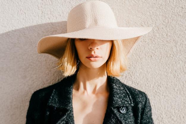 Retrato de menina loira elegante de cabelo curto com chapéu e jaqueta posando sobre bege