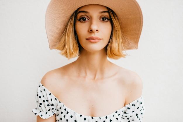 Retrato de menina loira elegante de cabelo curto com chapéu e vestido posando sobre fundo branco