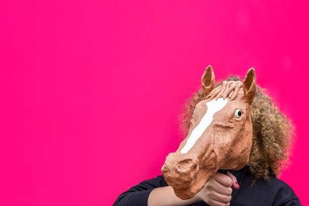 Retrato de menina loira encaracolada segurando o brinquedo da cabeça de cavalo