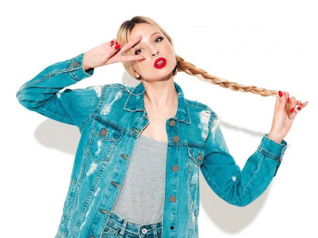 Retrato de menina má hipster jovem bonita em roupas da moda jeans e brinco no nariz. modelo positivo se divertindo. mostra o sinal de paz