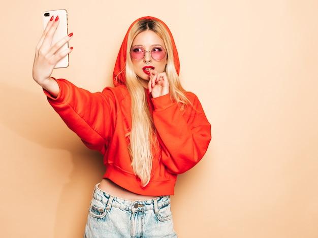 Retrato de menina má hipster jovem bonita em roupas da moda jeans e brinco no nariz. mulher loira sorridente despreocupada sexy leva selfie. modelo positivo lambendo doces de açúcar redondos