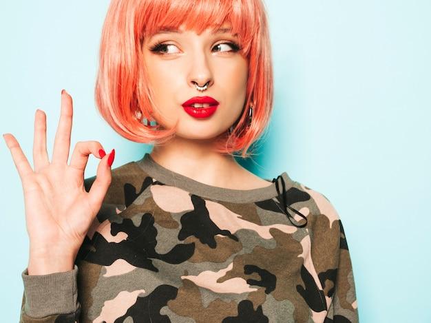 Retrato de menina má hipster jovem bonita em roupas da moda vermelho verão e brinco no nariz. mulher sorridente despreocupada sexy posando no estúdio na peruca rosa. modelo positivo mostra sinal de ok