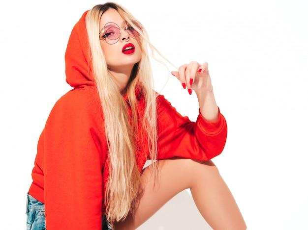 Retrato de menina má hipster jovem bonita no capuz vermelho na moda e brinco no nariz. mulher loira sorridente despreocupada sexy sentada no estúdio. modelo positivo se divertindo. isolado no branco