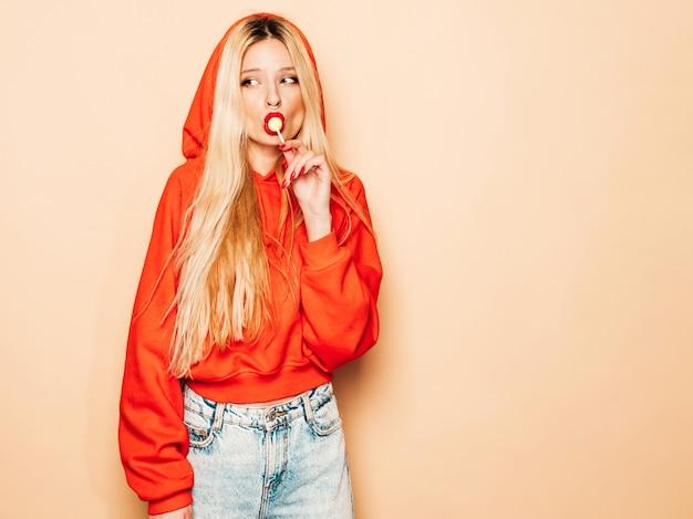 Retrato de menina má jovem hippie bonito no capuz vermelho na moda e brinco no nariz. modelo positivo lambendo doces de açúcar redondos